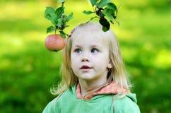 La niña mira cuidadosamente la manzana Fotografía de archivo libre de regalías