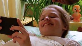 La niña mira el smartphone las negociaciones al papá Engendre las negociaciones a la hija y la besa almacen de video