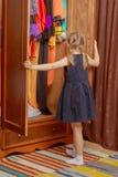 La niña mira en el guardarropa Fotos de archivo