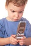 La niña mira en el teléfono celular Foto de archivo libre de regalías