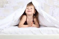 La niña mira hacia fuera de debajo la manta en cama Fotos de archivo