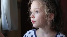 La niña mira hacia fuera la ventana almacen de metraje de vídeo