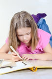 La niña mira un álbum de foto Fotos de archivo libres de regalías