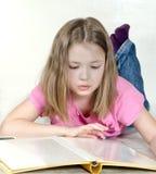 La niña mira un álbum de foto Fotografía de archivo