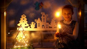 La niña mira la vela y sueños Árbol de navidad de las decoraciones del Año Nuevo almacen de metraje de vídeo