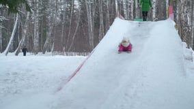 La niña monta rápidamente en la diapositiva del hielo metrajes
