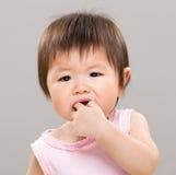 La niña muerde su finger Foto de archivo libre de regalías