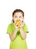 La niña muerde una manzana roja grande y mira a un lado Foto de archivo libre de regalías