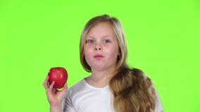 La niña muerde una manzana y muestra los pulgares para arriba Pantalla verde Cámara lenta metrajes
