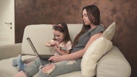 La niña muestra algo a su madre en el ordenador portátil almacen de video