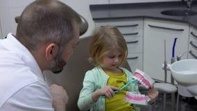 La niña muestra cómo ella cepilla sus dientes almacen de video
