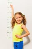 La niña muestra cómo ella crecerá este año imagen de archivo