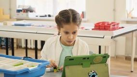 La niña muestra en su ipad la construcción plástica nessesary para la cámara lenta de la lección educativa metrajes