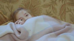La niña oculta debajo de la manta y come el mandarín almacen de metraje de vídeo