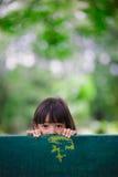 La niña ocultaba detrás de una silla en el parque Imagen de archivo