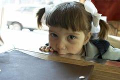 La niña ofendida se ha sostenido la lengüeta Foto de archivo libre de regalías
