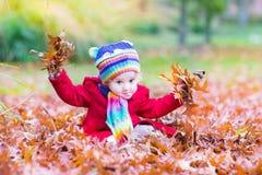 La niña pequeña adorable con rojo se va en parque del otoño Fotos de archivo libres de regalías