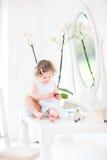 La niña pequeña bonita con el pelo rizado que juega con compone fotos de archivo libres de regalías
