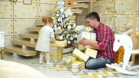 La niña pequeña con el padre puso las cajas de regalo debajo del árbol de navidad adornado en casa almacen de metraje de vídeo