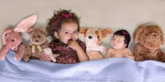 La niña pequeña gesticula para la tranquilidad mientras que duerme la hermana del bebé fotografía de archivo