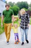 La niña pequeña que aprende andar en monopatín con sus jóvenes parents al aire libre imágenes de archivo libres de regalías