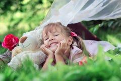 La niña plantea la mentira al aire libre con un oso y risas de peluche fotografía de archivo libre de regalías