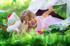 La niña plantea la mentira al aire libre en un tarva y risas imagen de archivo