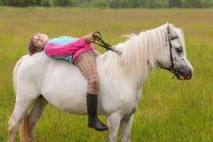 La niña pone en su caballo detrás blanco Imágenes de archivo libres de regalías