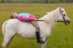 La niña pone en su caballo detrás blanco Fotos de archivo