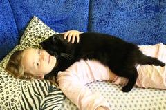 La niña pone y abraza su gato Foto de archivo