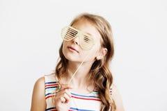 La niña preciosa en un vestido rayado con la foto divertida apoya el pap Imagen de archivo
