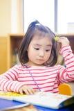La niña preciosa lee adentro la biblioteca Imágenes de archivo libres de regalías