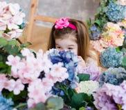 La niña preciosa, linda ocultó su cara detrás de un ramo de artifi Imagen de archivo libre de regalías