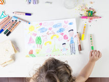 La niña que elegía un verde coloreó el lápiz en una tabla de madera para Fotografía de archivo libre de regalías