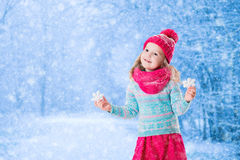 La niña que juega con nieve del juguete forma escamas en parque del invierno Foto de archivo libre de regalías