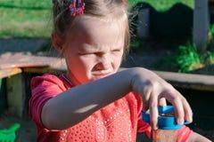 La niña que juega en la arena y tamiza la arena a través de un tamiz Fotos de archivo libres de regalías