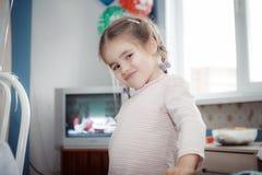 La niña que juega en casa, las caras retuerce imágenes de archivo libres de regalías