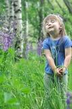 La niña que juega en lupine floreciente soleado de la cosecha del niño del niño del bosque florece juego de los niños al aire lib Fotografía de archivo libre de regalías