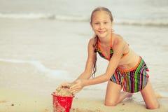 La niña que jugaba con la arena de los juguetes fijó en la playa Fotografía de archivo