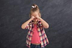 La niña que llora y que cubre observa con las manos Imágenes de archivo libres de regalías