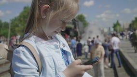 La niña que mira su teléfono elegante en un rato de la estación de tren está esperando almacen de video