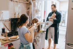 La niña que permanece en el taburete ayuda a su madre que cocina las crepes para el desayuno y el padre con el bebé en sus brazos imagen de archivo