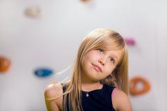 La niña que presenta en una sala de juegos Imagenes de archivo