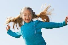 La niña que salta al aire libre Imagenes de archivo