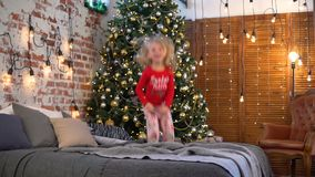 La niña que salta en la cama cerca del árbol de navidad almacen de video