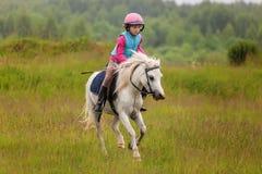 La niña que salta en el campo en un galope Fotos de archivo