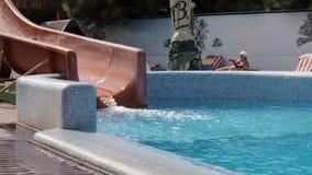 La niña que salta en la piscina con las diapositivas almacen de metraje de vídeo