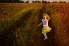 La niña que salta en un campo del verano en emociones buenas de un humor Imagen de archivo libre de regalías