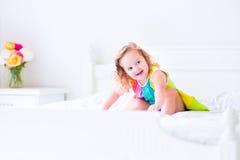 La niña que salta en una cama Imagen de archivo