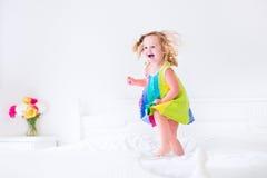 La niña que salta en una cama Fotos de archivo libres de regalías
